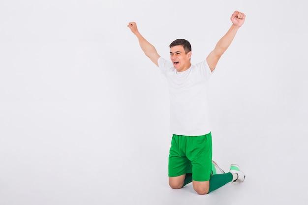 Jogador de futebol comemorando com os braços levantados
