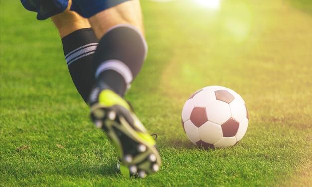 Jogador de futebol correndo jogando cruzado na grama