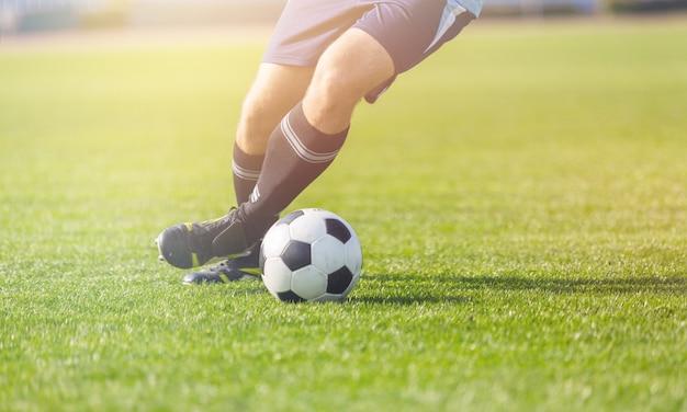 Jogador de futebol correndo na grama
