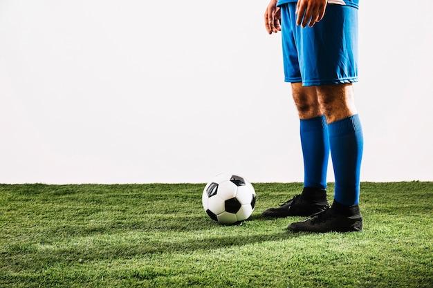 Jogador de futebol de colheita perto de bola