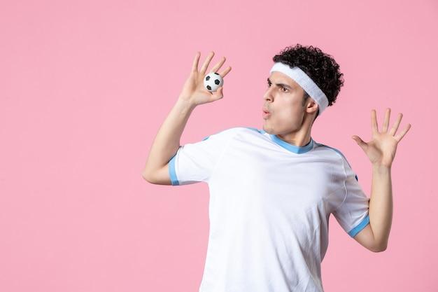 Jogador de futebol de frente com roupas esportivas e bolinha
