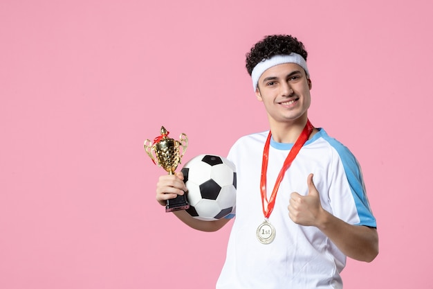Jogador de futebol de vista frontal com roupa esporte com taça de ouro e medalha
