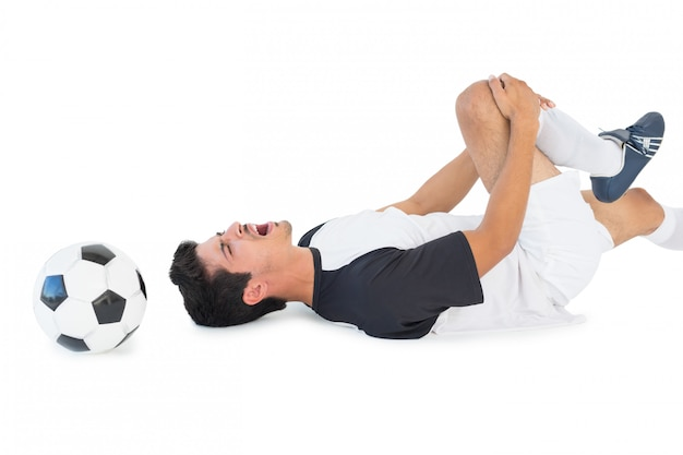 Jogador de futebol deitado e gritando de dor