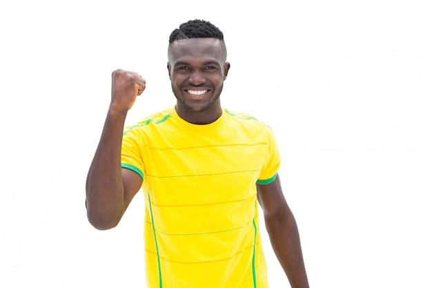 Jogador de futebol em amarelo comemorando uma vitória