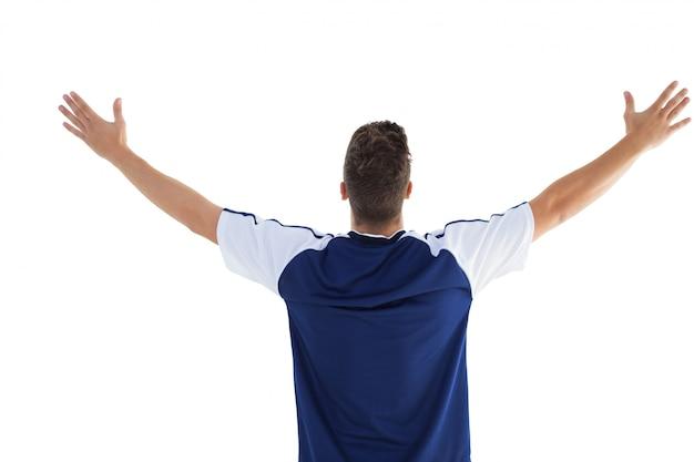 Jogador de futebol em azul comemorando uma vitória