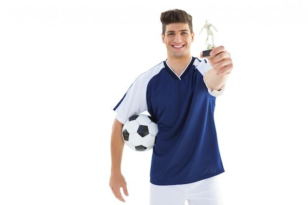 Jogador de futebol em azul jersey segurando troféu de vencedores