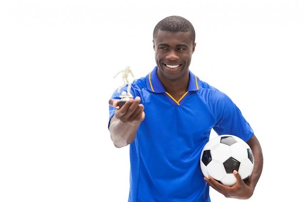 Jogador de futebol em bola azul e estatueta