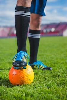 Jogador de futebol em estádio com pé na bola