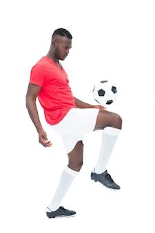 Jogador de futebol em jersey vermelho controlando bola