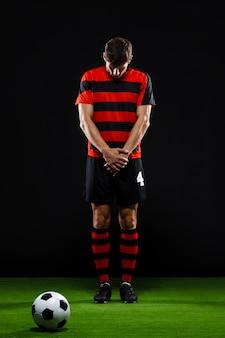 Jogador de futebol em pé no pontapé livre perto da bola, goleiro seguro