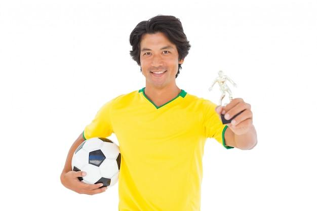 Jogador de futebol em troféu de ganhadores amarelos