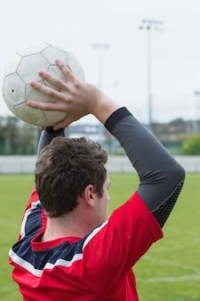 Jogador de futebol em vermelho jogando da linha lateral