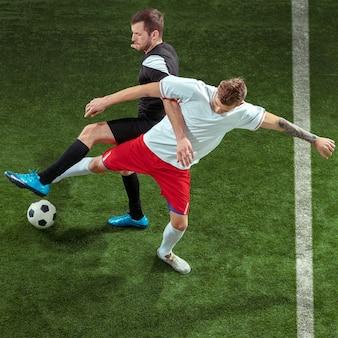 Jogador de futebol, enfrentando a bola sobre o fundo da grama verde.