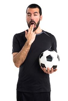 Jogador de futebol fazendo um gesto de vômito