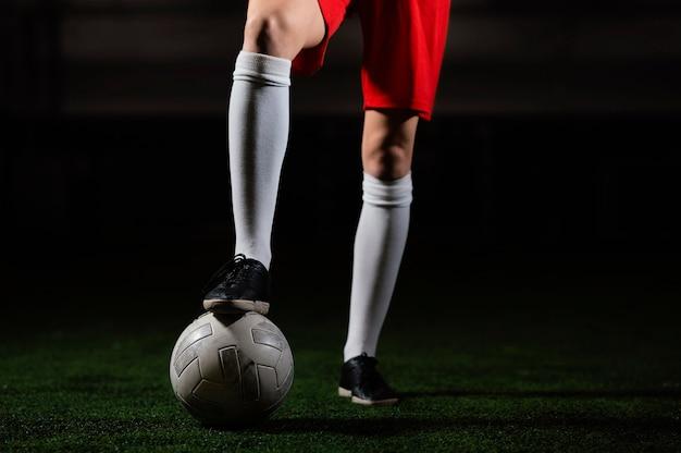Jogador de futebol feminino com bola de perto