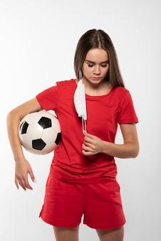 Jogador de futebol feminino com máscara segurando uma bola