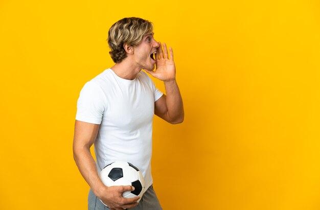 Jogador de futebol inglês em amarelo isolado gritando com a boca bem aberta para o lado