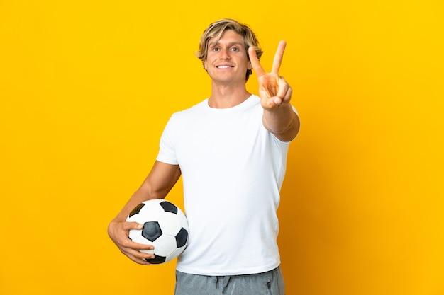 Jogador de futebol inglês isolado amarelo sorrindo e mostrando sinal de vitória