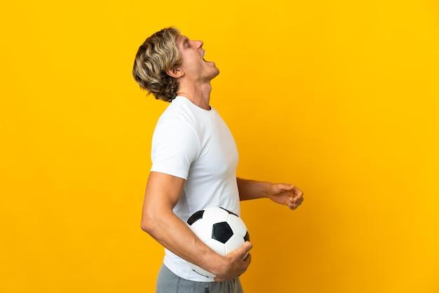 Jogador de futebol inglês sobre amarelo rindo na posição lateral