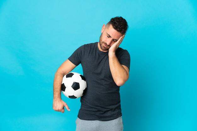 Jogador de futebol isolado em fundo azul com dor de cabeça