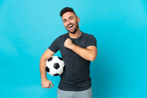 Jogador de futebol isolado em fundo azul comemorando vitória