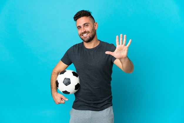 Jogador de futebol isolado em fundo azul contando cinco com os dedos