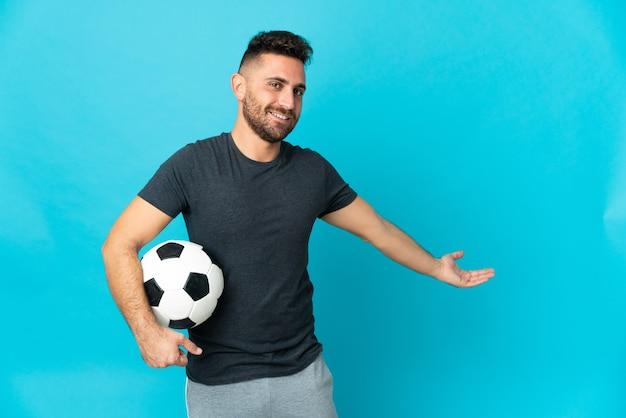 Jogador de futebol isolado em fundo azul estendendo as mãos para o lado para convidar para vir
