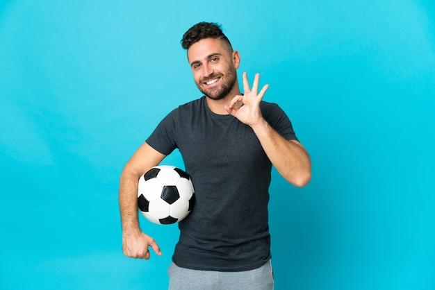 Jogador de futebol isolado em fundo azul mostrando sinal de ok com os dedos