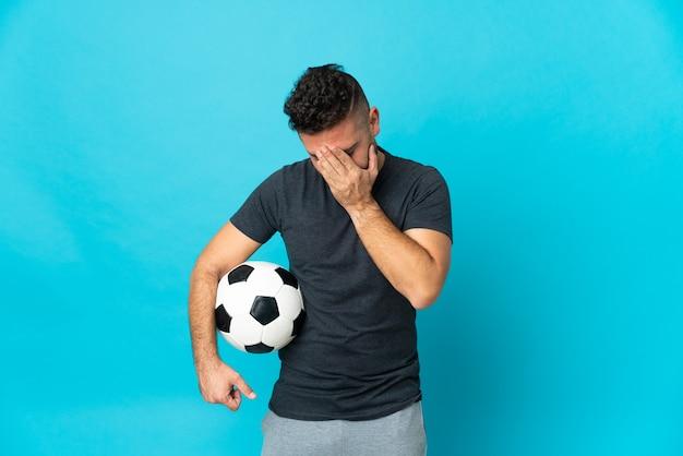 Jogador de futebol isolado em um fundo azul com expressão cansada e doente