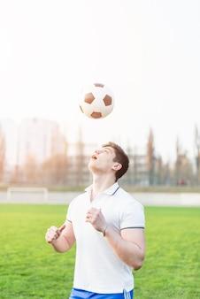 Jogador de futebol jogando bola sobre a cabeça
