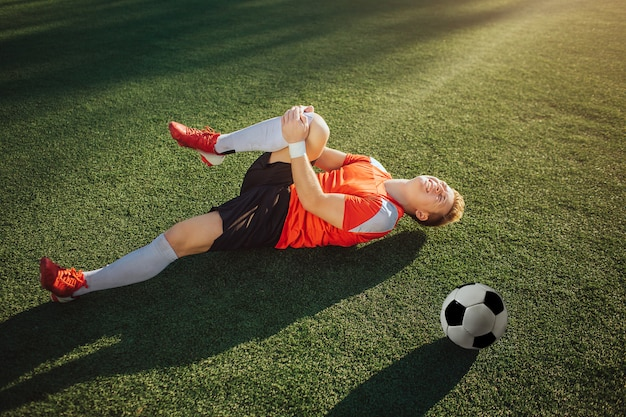 Jogador de futebol jovem deitado no gramado e segure a perna. ele puxa para si mesmo. cara sente dor no joelho. bola deitada ao lado dele.