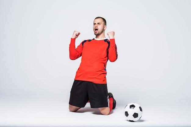 Jogador de futebol jovem e animado com a camisa vermelha comemorando o gol