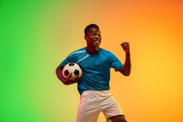 Jogador de futebol masculino afro-americano imparável treinando em ação