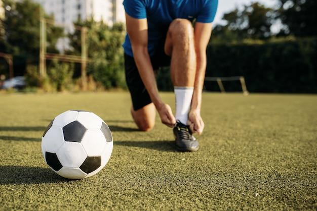 Jogador de futebol masculino amarra o cadarço nas botas, vista superior. jogador de futebol no estádio ao ar livre, treino antes do jogo, treino de futebol