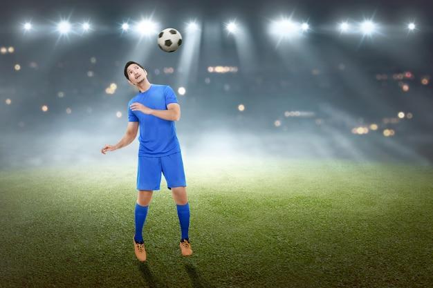 Jogador de futebol masculino asiático bonito tentando encabeçar a bola