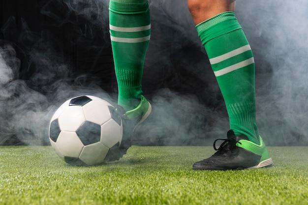 Jogador de futebol no sportswear com bola de futebol