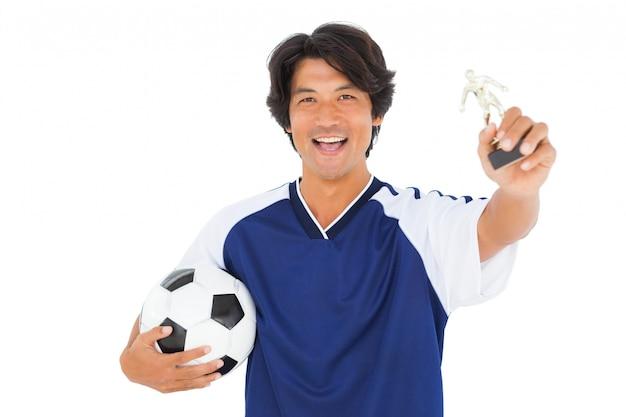 Jogador de futebol no troféu azul dos ganhadores