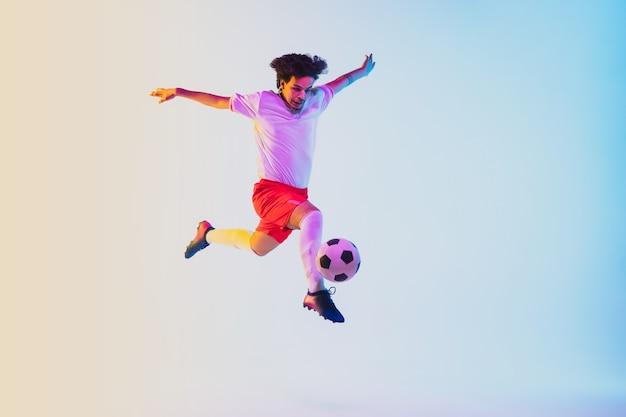 Jogador de futebol ou futebol em fundo gradiente no conceito de atividade de ação de movimento de luz de néon