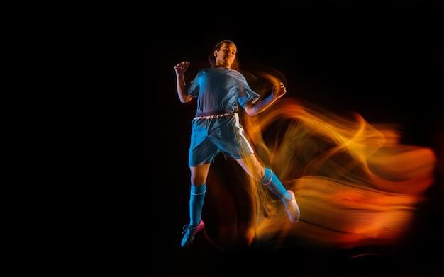 Jogador de futebol ou futebol no estúdio preto