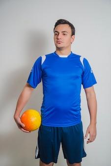 Jogador de futebol posando com bola