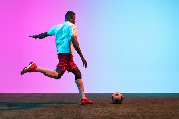 Jogador de futebol profissional de futebol de um homem treinando isolado em parede gradiente