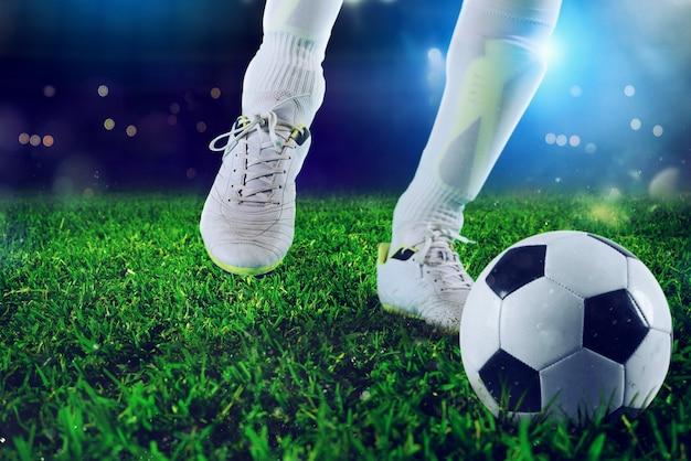 Jogador de futebol pronto para chutar a bola de futebol no estádio