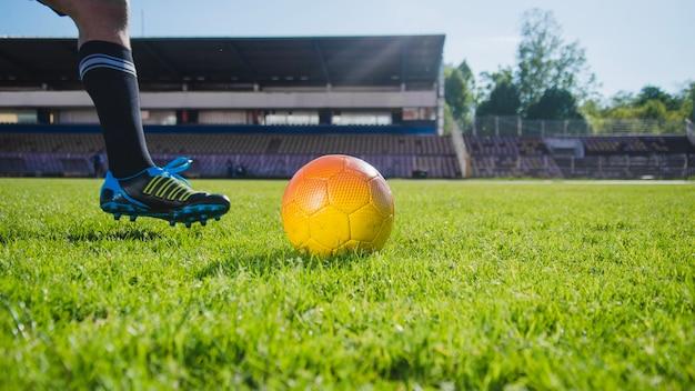 Jogador de futebol que chuta a vista da perna