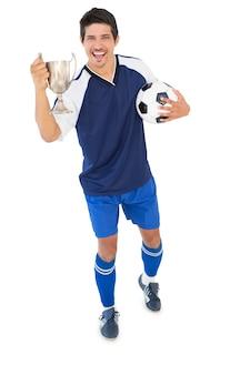Jogador de futebol segurando copo de vencedores
