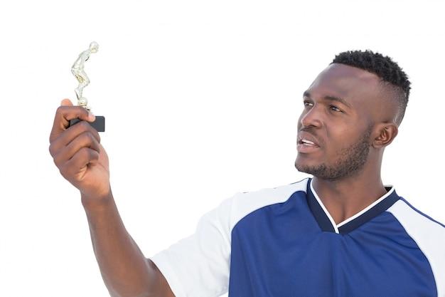 Jogador de futebol segurando o troféu dos vencedores