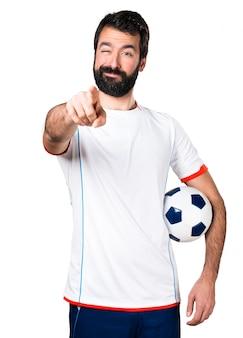 Jogador de futebol segurando uma bola de futebol apontando para a frente