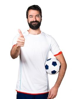 Jogador de futebol segurando uma bola de futebol com o polegar para cima