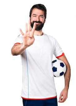 Jogador de futebol segurando uma bola de futebol contando quatro