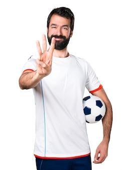 Jogador de futebol segurando uma bola de futebol contando três