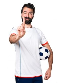 Jogador de futebol segurando uma bola de futebol contando um